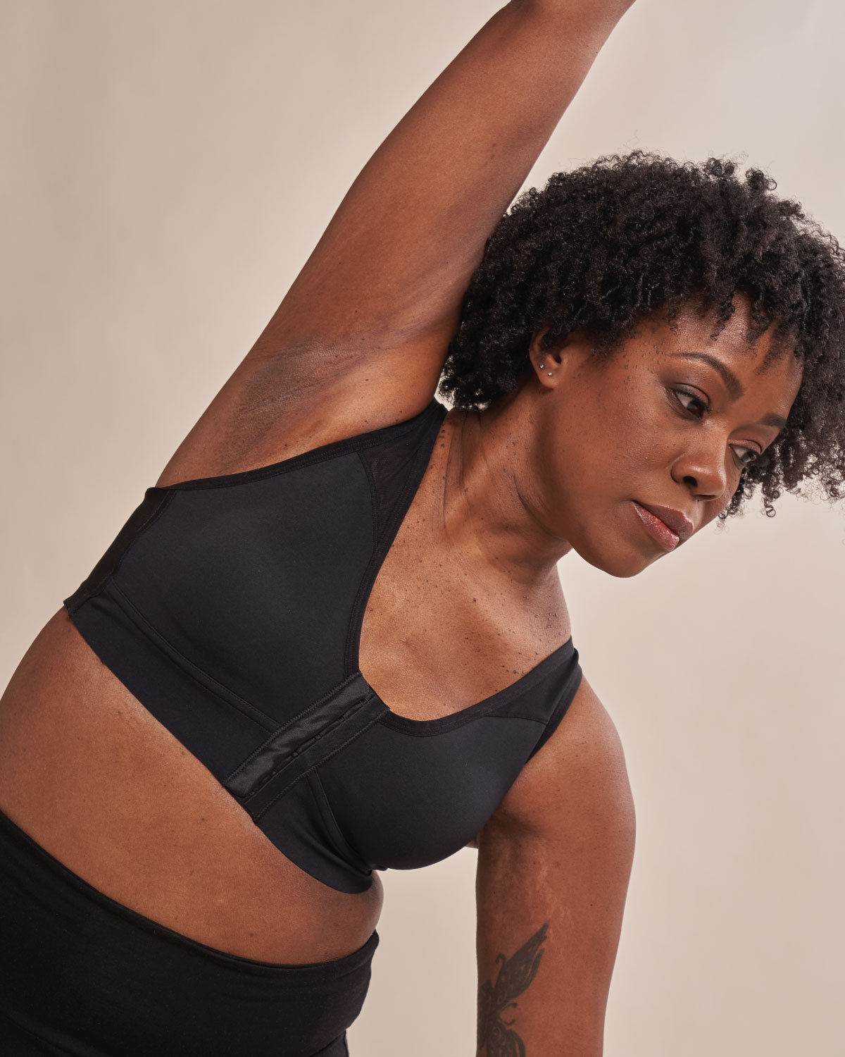 Black, pocketed front closure sports bra with adjustable straps, mesh paneling on cross back, soft material and wireless cups on flap reconstruction model.