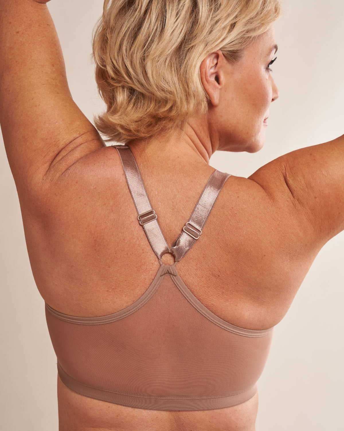 Sand, pocketed front closure sports bra with soft wireless cups, adjustable straps and mesh paneling on cross back, on a flap reconstructed model.
