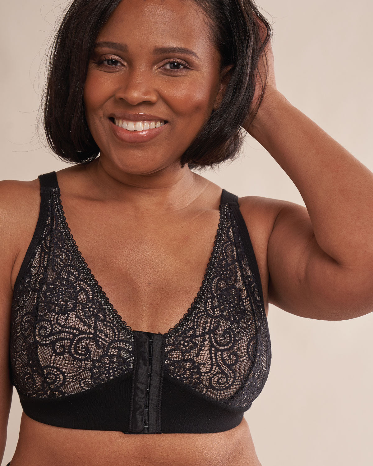 Black, pocketed front closure lace bra made with soft modal, dual adjustable back straps and underwire free cups on model with implants.