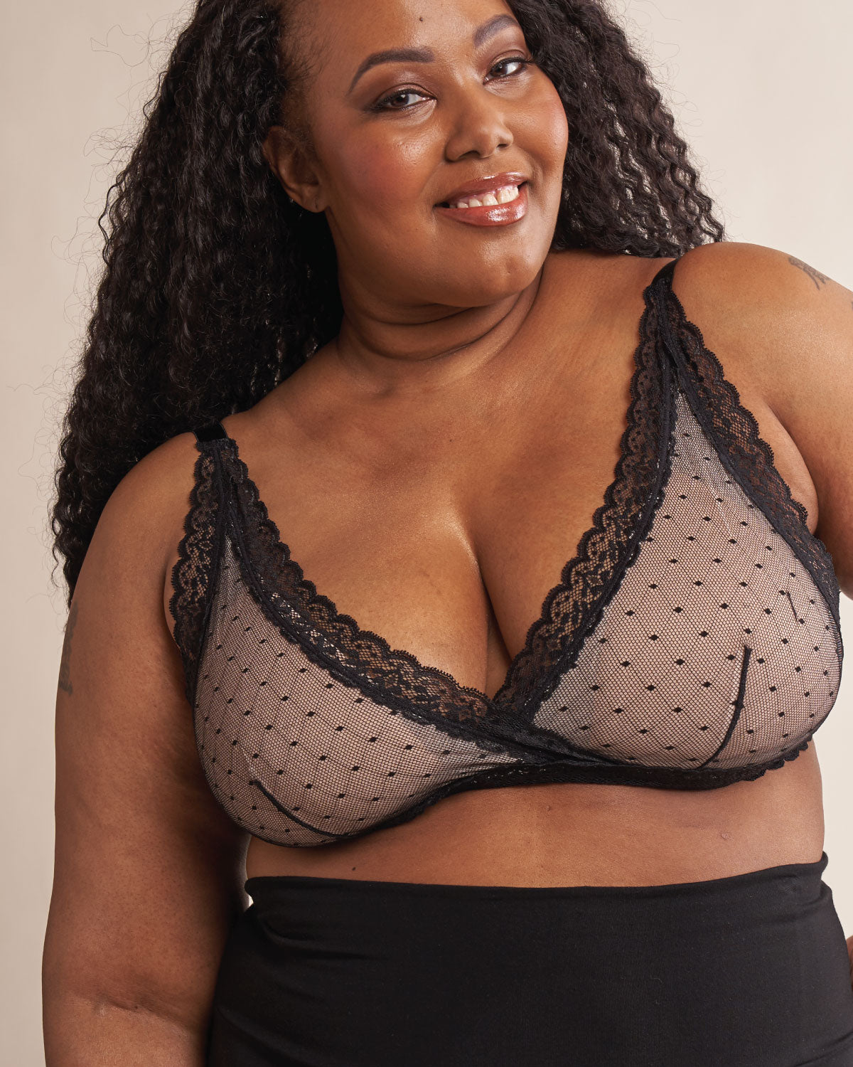 Black, pocketed wrap front lace bralette with wireless cups, back closure and adjustable straps on model.