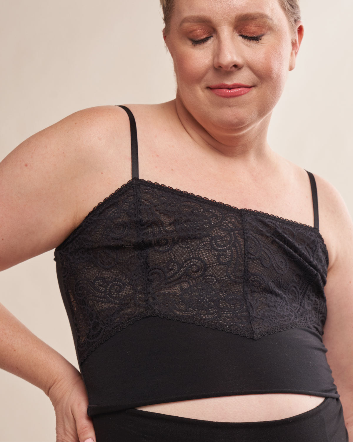 Black, pocketed cropped lace cami with adjustable straps, lettuce hem detail and soft modal on flat chest model.