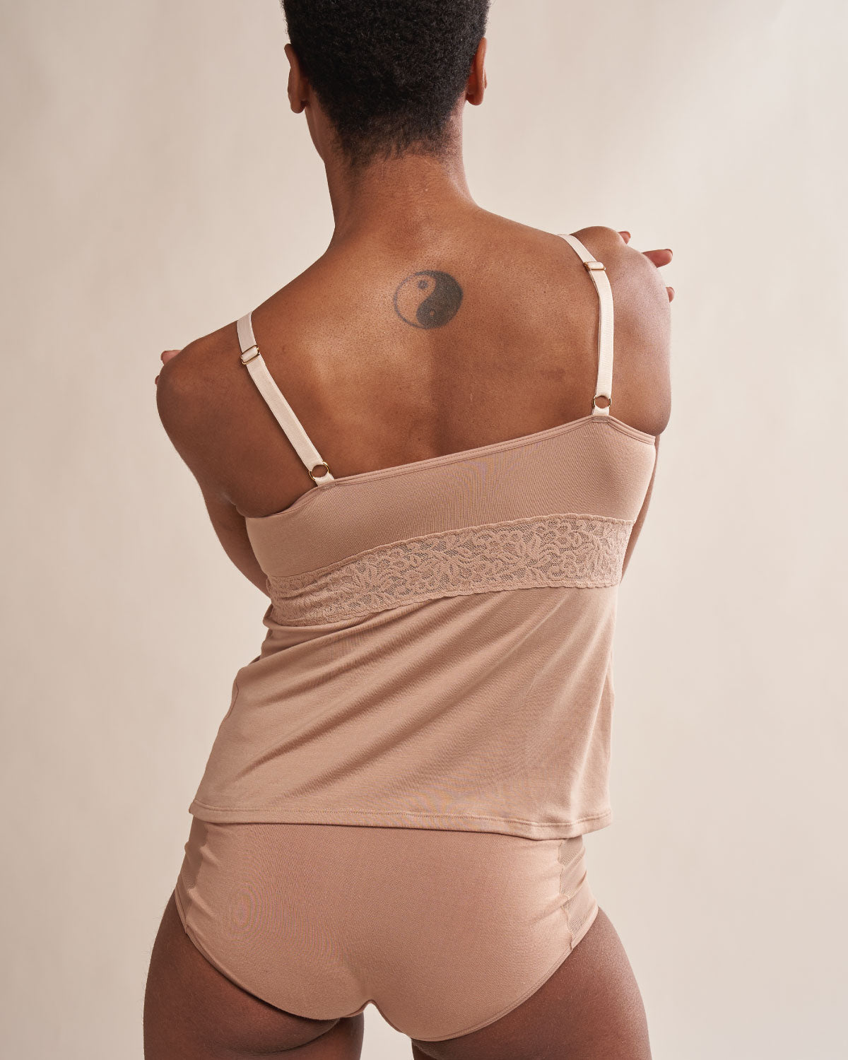 Sand, pocketed camisole with wireless cups, wrap front design, lace v neck and adjustable straps.