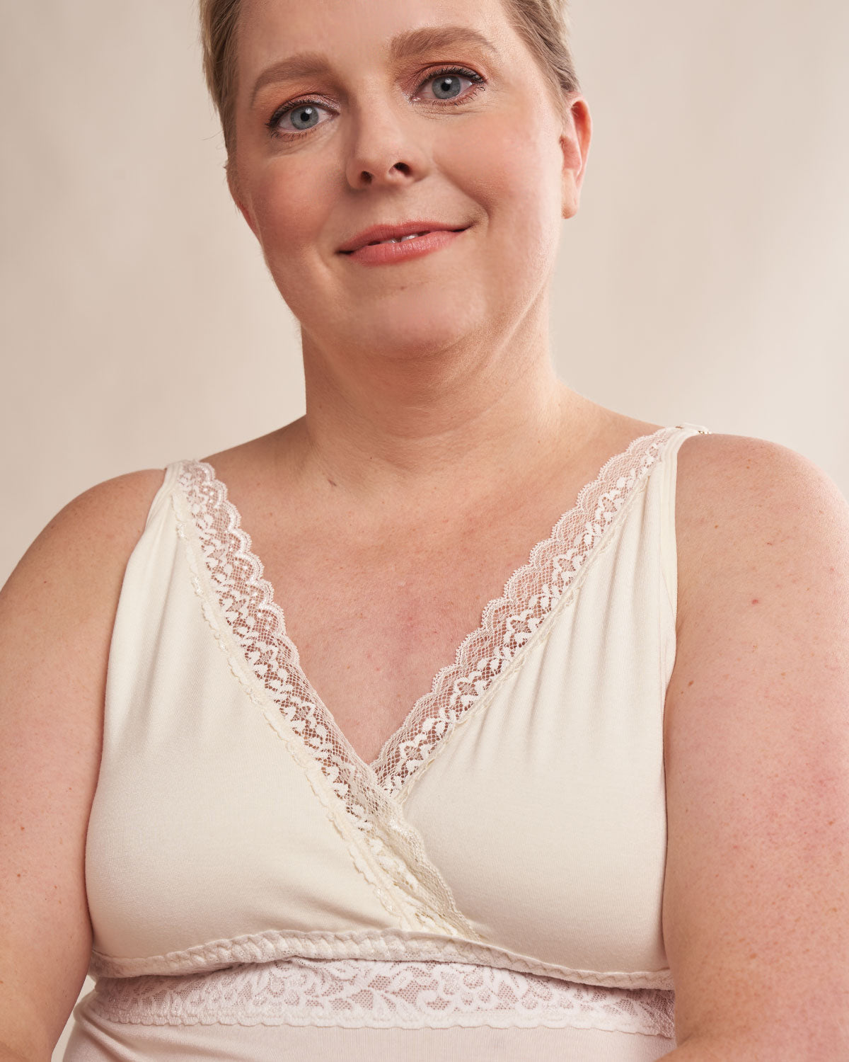 Ivory, pocketed camisole with wireless cups, wrap front design, lace v neck and adjustable straps on mastectomy model.