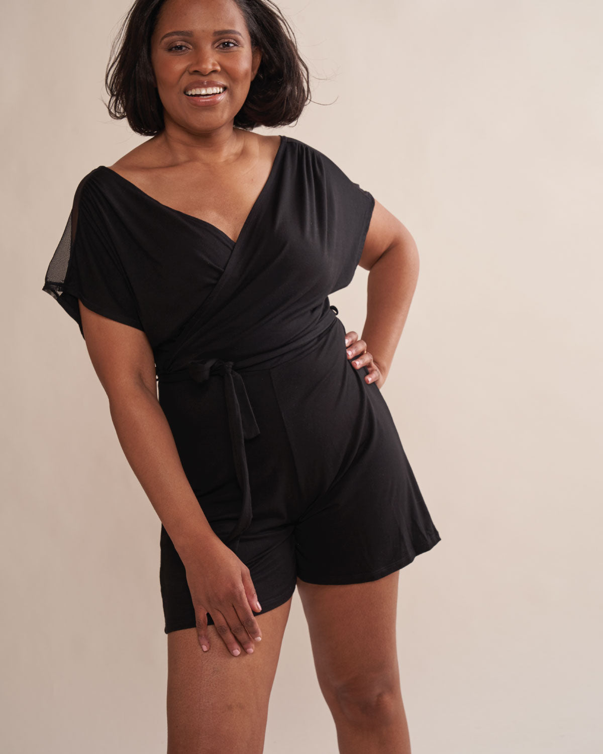 Black, wrap front soft modal romper with mesh shoulders, wide armholes, tie belt and attachable drain belt.
