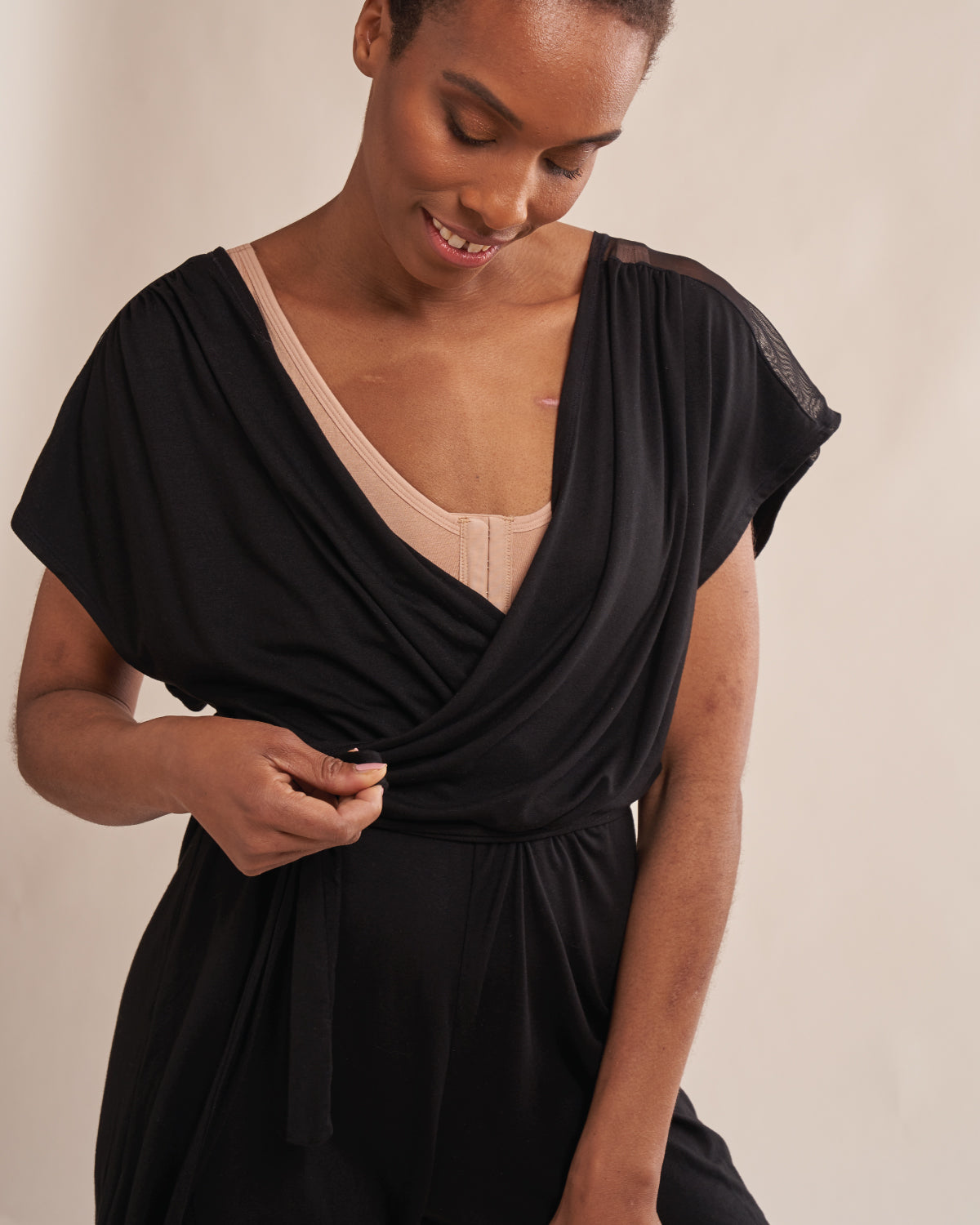 Black, wrap front soft modal romper with mesh shoulders, wide armholes, tie belt and attachable drain belt for after surgery recovery.