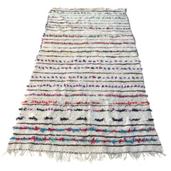 beige moroccan rug with colorful tassels