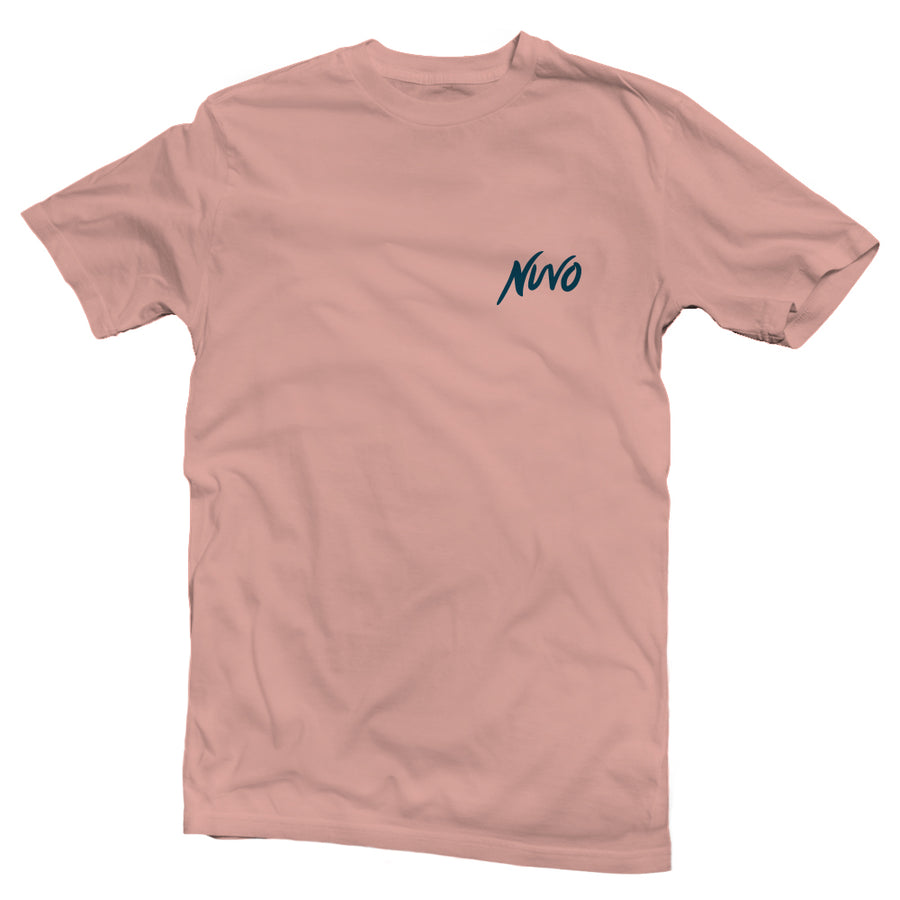 The back of a desert pink, Nuvo brand, short sleeve graphic t-shirt featuring mountain and lake scene inside of arrowhead shape