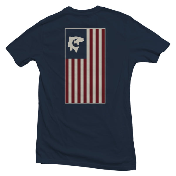 The back of a navy blue, Nuvo brand, short sleeve graphic t-shirt featuring a large, vertical American flag with a fish and hook in top left corner
