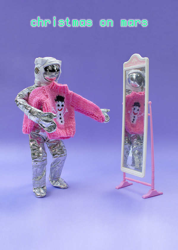Christmas on Mars - astronaut tries on pink jumper in front of mirror