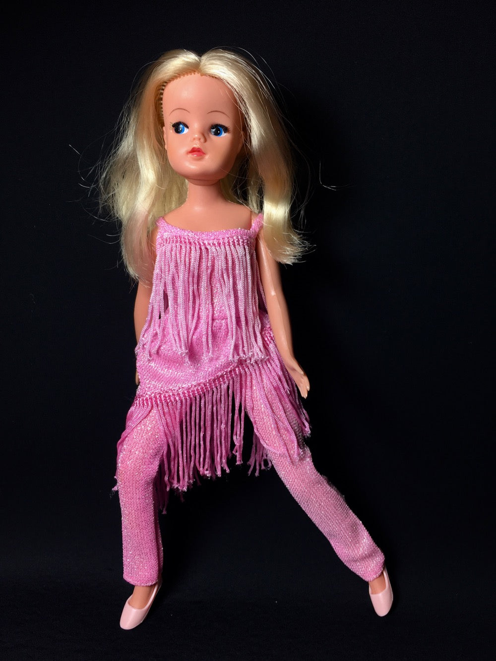 Sindy in pink glitter jumpsuit dress with tassels.