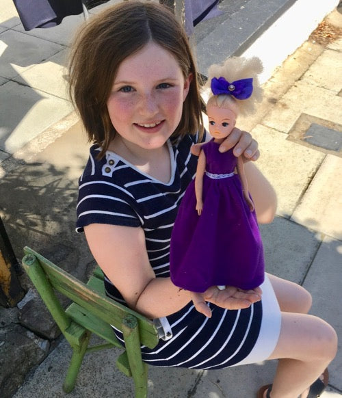 Young girl with Sindy doll in purple outfit.