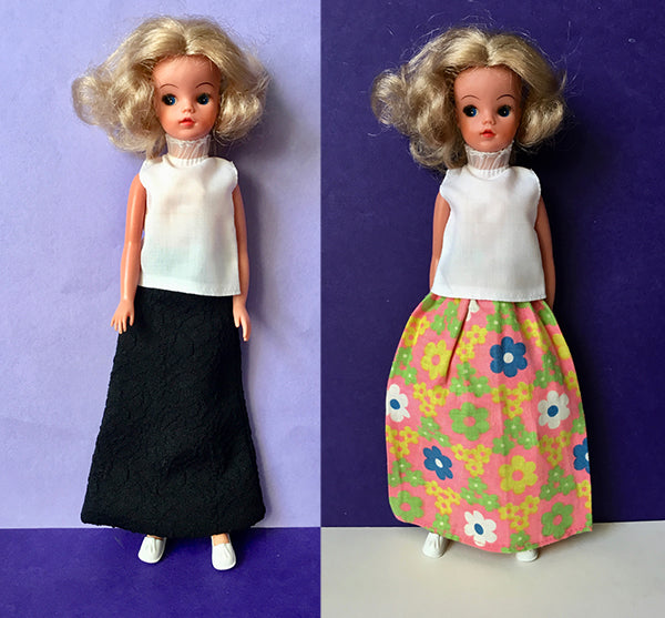 Two Sindy dolls modelling flower power maxi and black maxi skirts