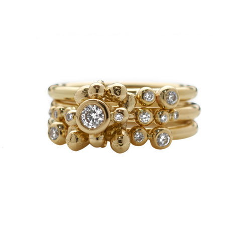 A multitude of diamonds set upon 18ct gold bands. Indulgent yet elegant and fresh. Here Yen Jewellery demonstrates a unique way to stack rings.