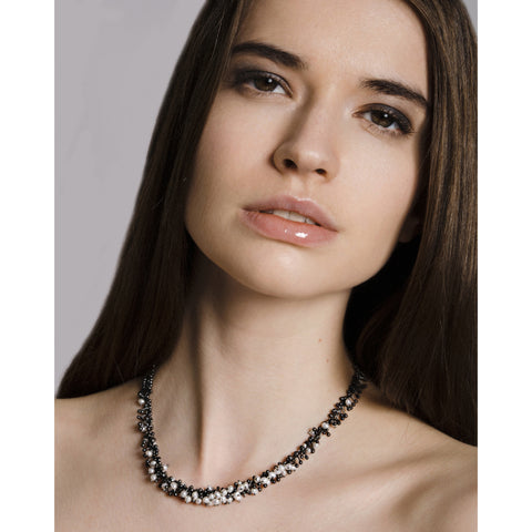 Model wears a handmade oxidised silver and freshwater pearl necklace. The chain is made up of hundreds of handmade silver droplets.
