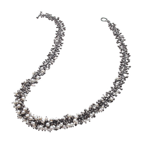A handmade oxidised silver and freshwater pearl necklace. Beads and droplets of pearl and silver form a dense cluster necklace.