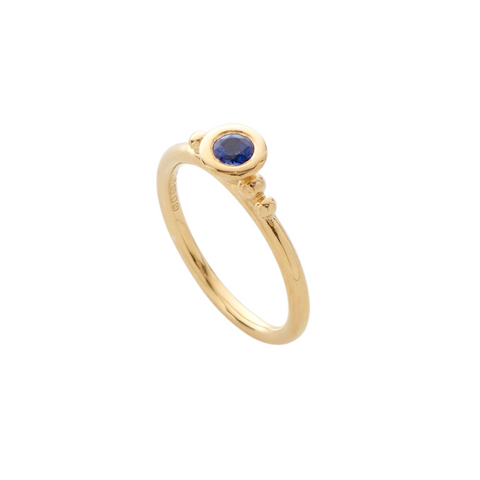 An 18ct yellow gold ring set with a deep, rich blue sapphire. 18ct gold bud-like detail surrounds the precious gemstone. From the recent Aestivation collection by Yen Jewellery, London.
