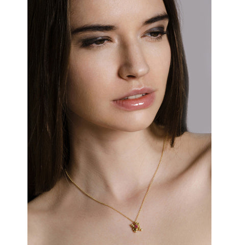 Model wears the ruby and 18ct droplet necklace. One ruby gemstone nestled in a cluster of 18ct gold moving parts.