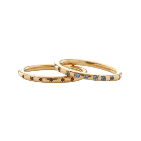 Two 18ct yellow gold bands, one with flush-set rubies, the other with topaz. These rings stack perfectly together or can be worn alone as elegant adornment.