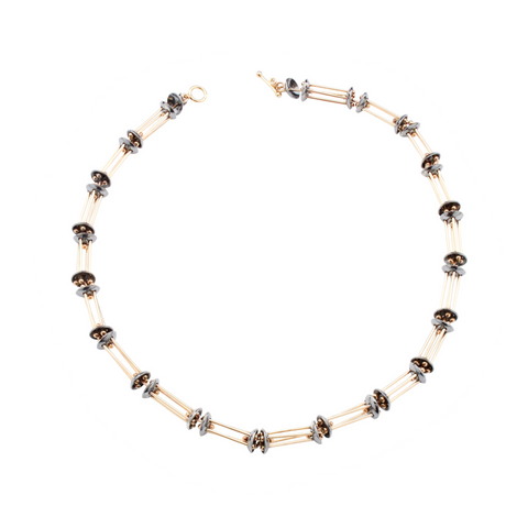 9ct gold structured bars and oxidised silver domes form this modern and contemporary necklace. Designed and handmade by Yen Jewellery.