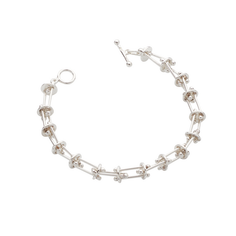 Silver domed disc are intricately connected to silver pillar-like bars. An interesting, unique bracelet that will match every outfit and occasion.
