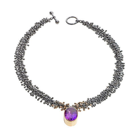 A large amethyst hangs off a handmade oxidised silver and gold chain. The chain consists of hundreds of recurring components.