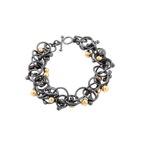Gold and oxidised silver spherical structures interwoven to form this dramatic bracelet. A bold statement piece. Handmade by Yen Jewellery.