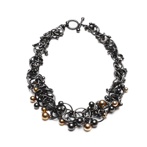Dense interwoven strands of oxidised silver and gold orbs. The mass thickens in the middle. The ultimate statement piece. Handmade by Yen Jewellery.