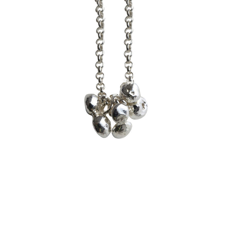 A drop pendant with delicate silver pebbles clustered at the centre. Handmade by Yen Jewellery