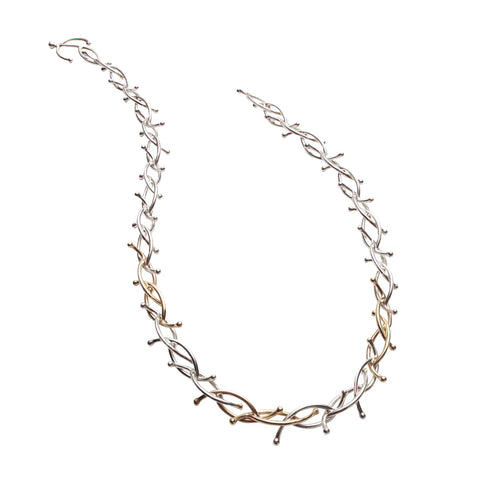 Interwoven strands of gold and silver form this striking necklace designed and handmade by Yen Jewellery, London.