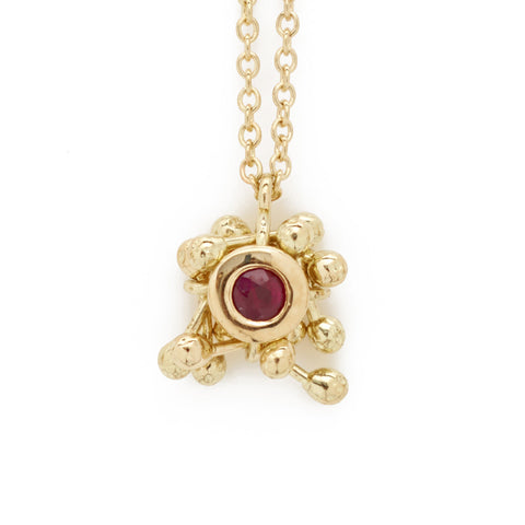 A small ruby drop pendant surrounded by a cluster of kinetic 18ct gold components. Designed and handmade by Yen Jewellery.