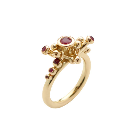 Nine rubies of various sizes set on an 18ct gold shank. The rubies are nestles around luxurious gold nodes, like a connection point or flowers waiting to bloom.