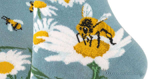 Give Bees a Chance Socks by ModSocks are slate blue crew socks covered in a design of bees and daisies, the flowers forming a big peace sign above the ankle.