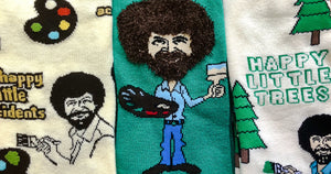 Bob Ross sock styles in cream and green featuring the PBS artist and icon with his paintbrush, palette and signature hair.