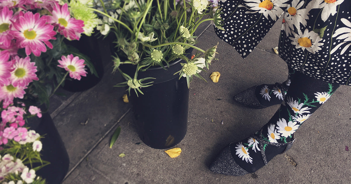Daisy flower socks with white flowers on a black background, next to florist's blooms.