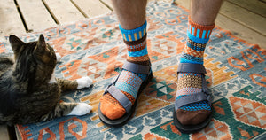 Extra large men's socks in a colorful mismatched pattern of blue and orange, worn with sandals.