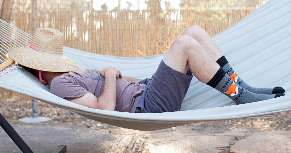 "A man lays on a hammock wearing ""Zero Fox Given"" men's socks"