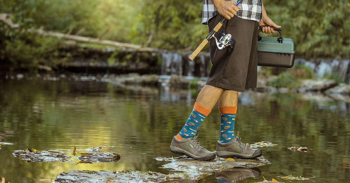 A man in fishing lure socks walks across a river with a fishing pole and tackle box.
