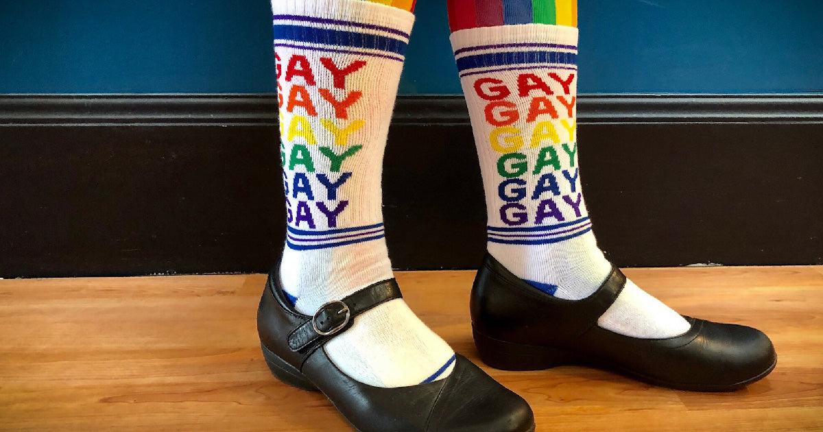 "Gay socks with the word ""GAY"" repeated in rainbow letters on white unisex socks"