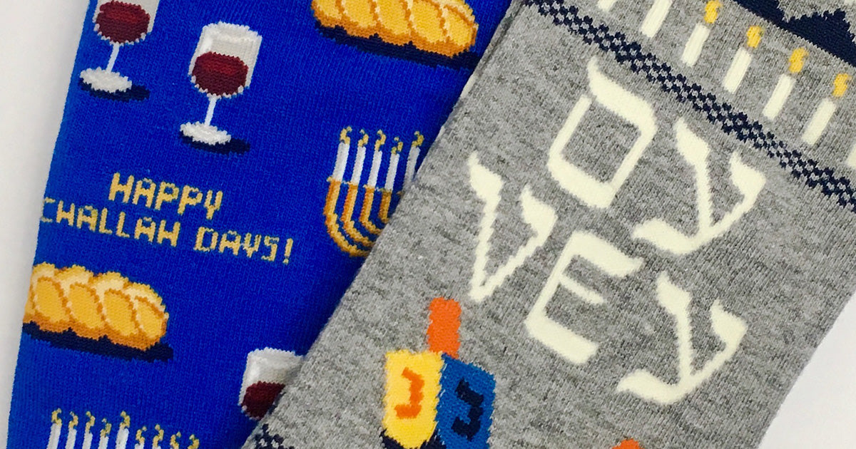 "Hanukkah socks with challah bread, a menorah, a dreidel and the words ""Oy vey."""