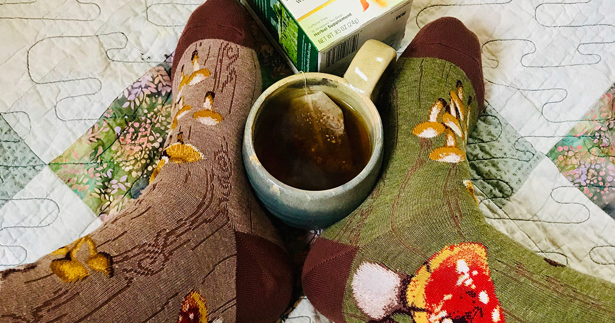 Mushroom socks and a cup of tea remind us to improve our foot wellbeing with foot wellness tips