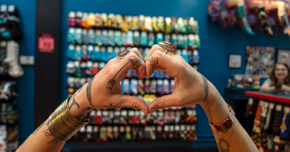 An employee makes a heart gesture with her hands in front of a wall of colorful socks at Cute But Crazy sock shop in Bellingham, Washington.