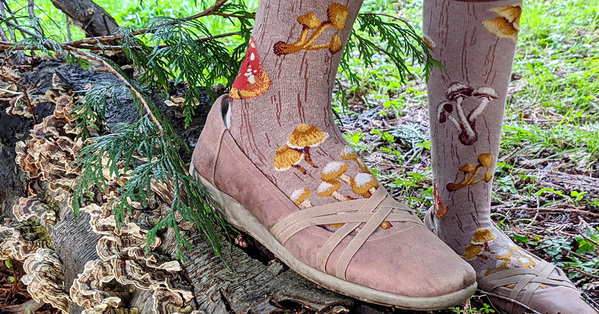 Feet in brown mushroom novelty socks and matching shoes stand on a log covered in small mushrooms