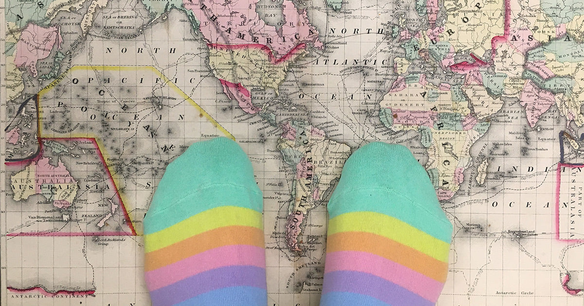 worldwide shipping illustration with pastel rainbow socks on a world map