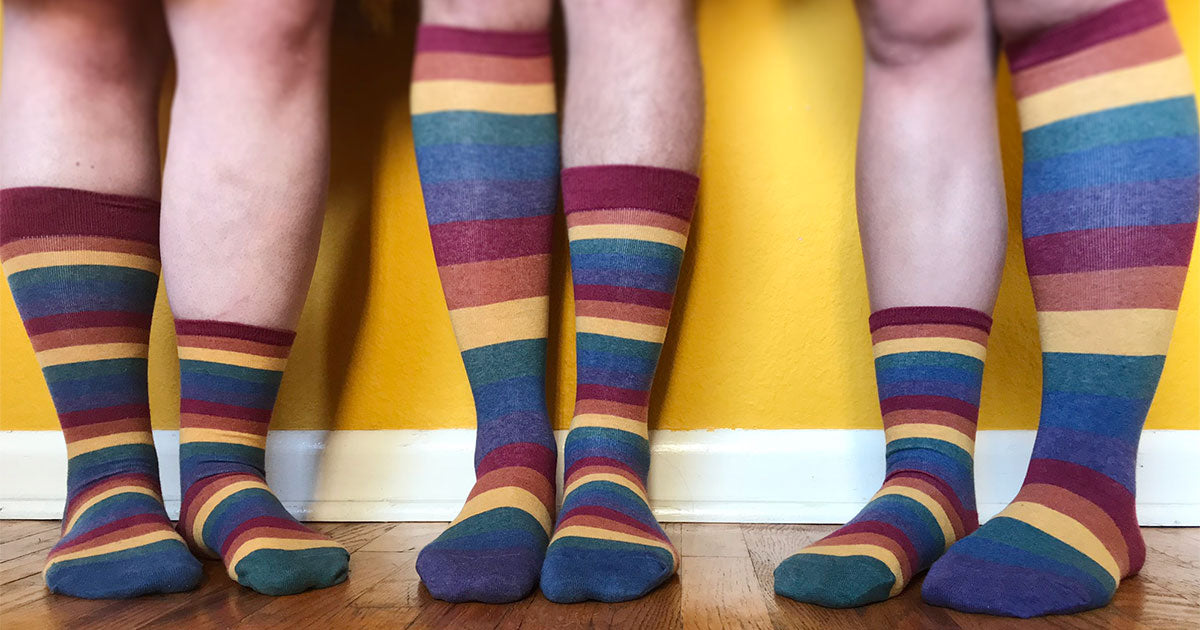 Muted rainbow-striped socks designed by ModSocks in sizes to fit men, women & non-binary people.