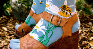 Bee socks with daisies and honeybees paired with brown floral embossed leather platform wedge sandals for a hippie-inspired look.