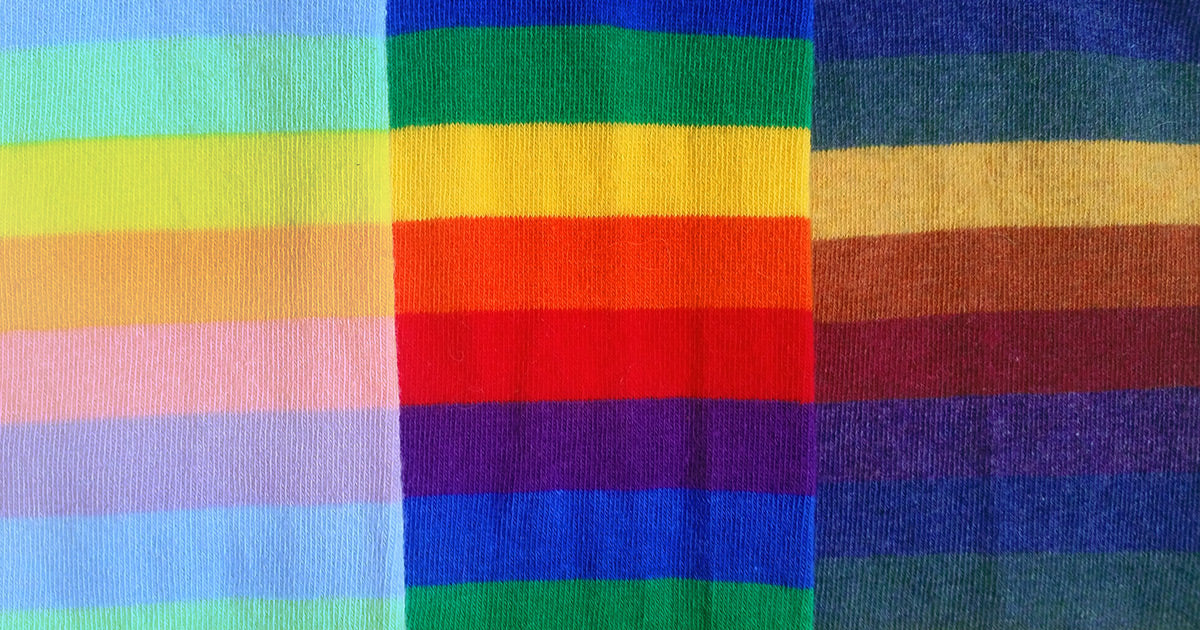 Three rainbow-striped socks in pastel, traditional and dark tones