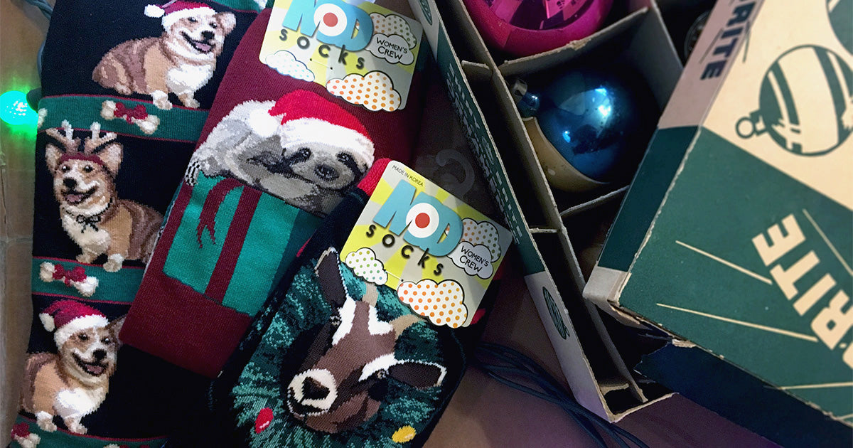 Christmas socks with animal designs featuring corgi dogs, Santa sloths and goats with Christmas lights.