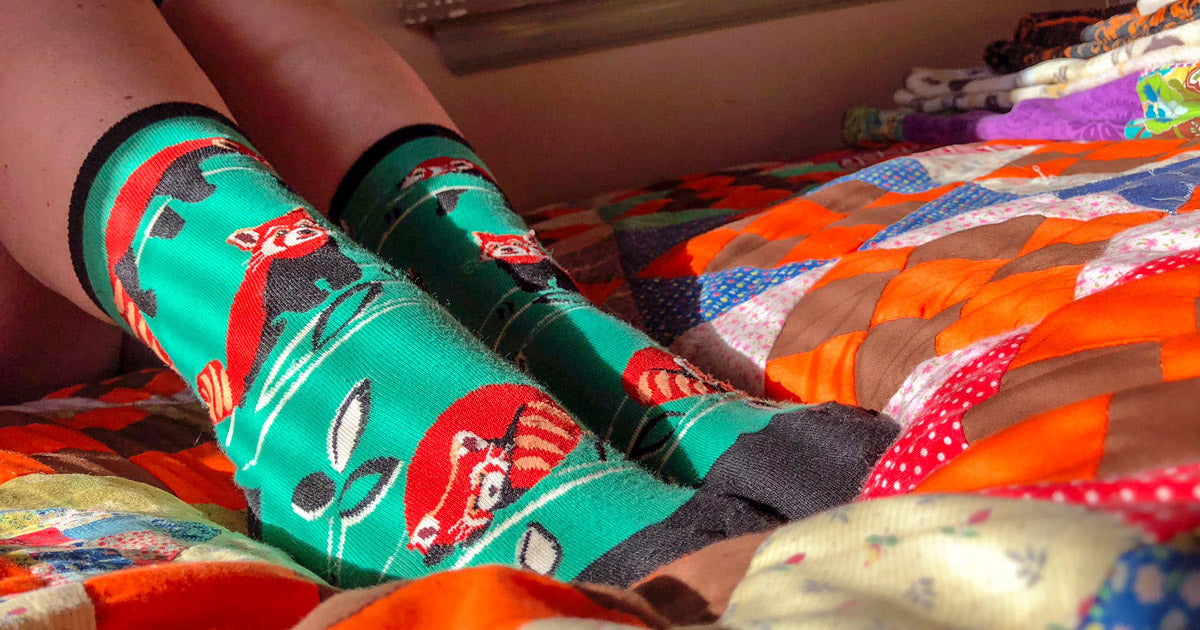 Woman wearing red panda socks in bed.