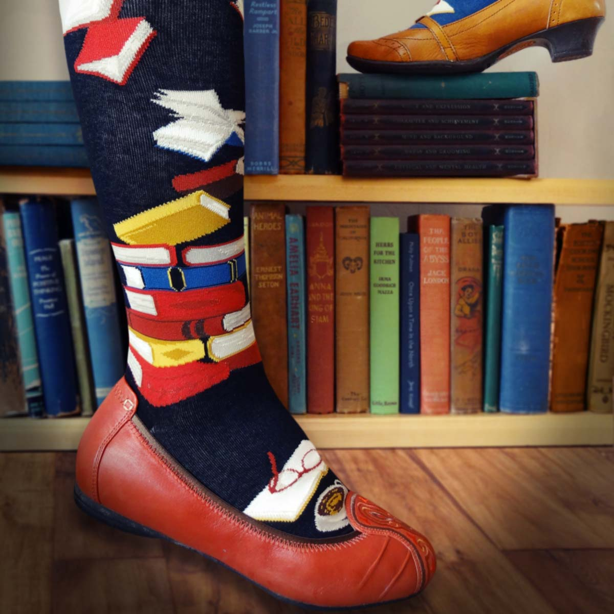 Book socks for women are black knee socks with red, yellow and blue books on them.