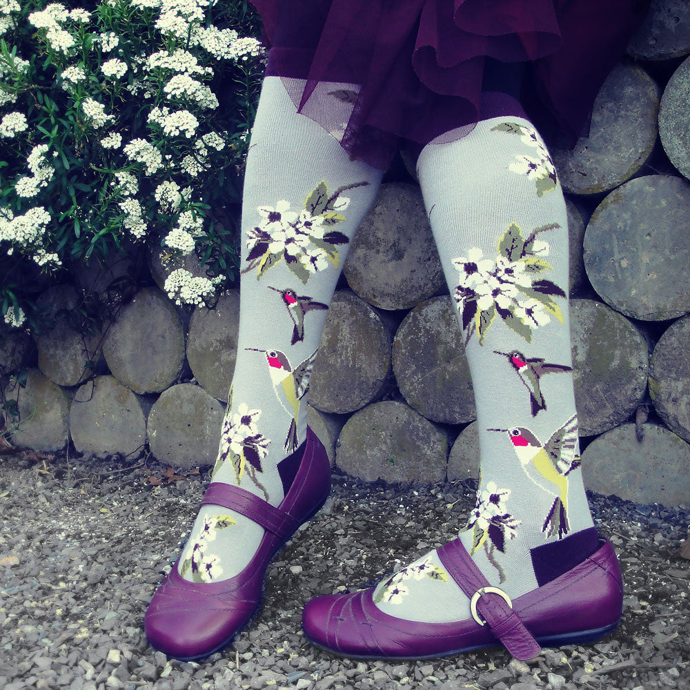 Our Bird Socks collection is the perfect pit stop when shopping for the bird lover in your life. These grey knee highs feature colorful hummingbirds flying to sip nectar from fresh white flowers and have a cute purple heel, toe, and cuff.